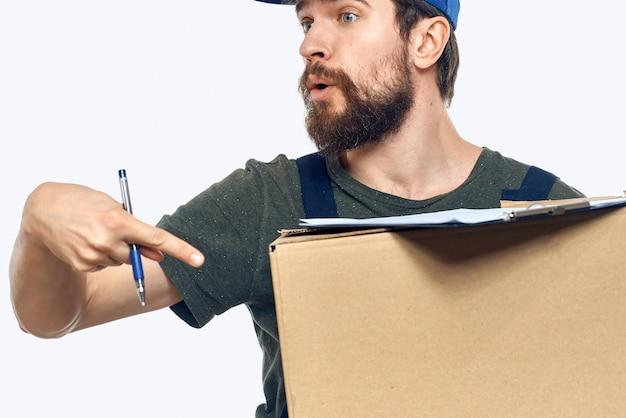 Hombre en el trabajo de mensajería cargador de entrega caja uniforme fondo claro. foto de alta calidad