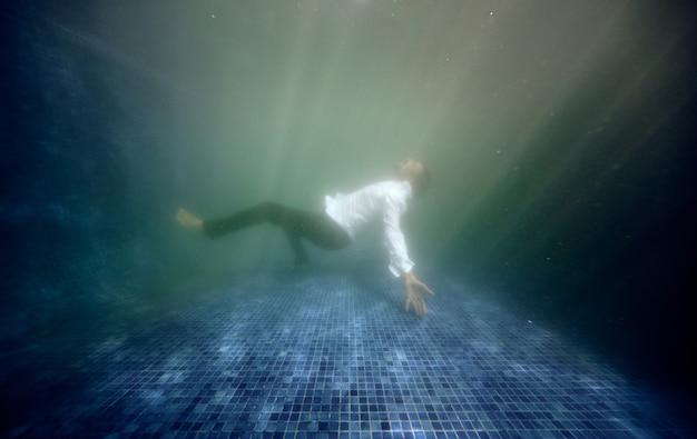 Hombre en traje ahogándose en el agua de la piscina