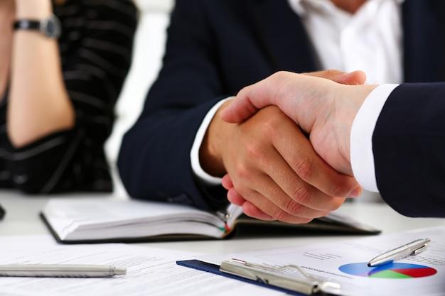 Hombre en traje de apretar la mano como hola en primer plano de la oficina