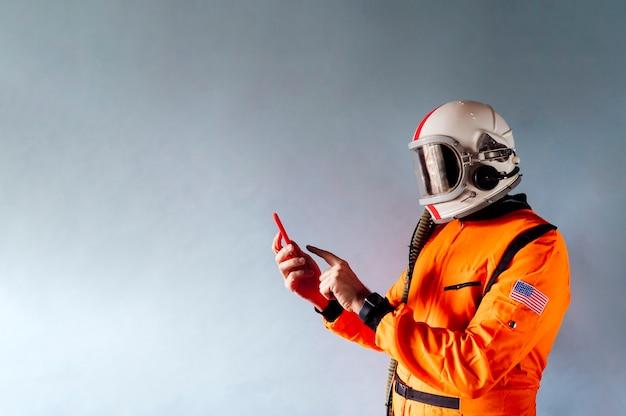 Hombre en traje de astronauta con un teléfono inteligente.