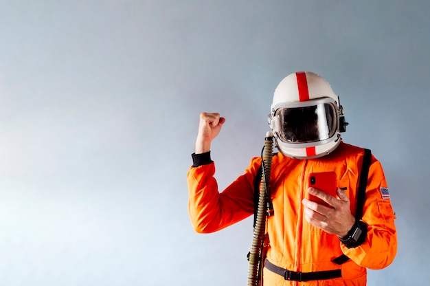 Hombre con traje de astronauta y teléfono móvil