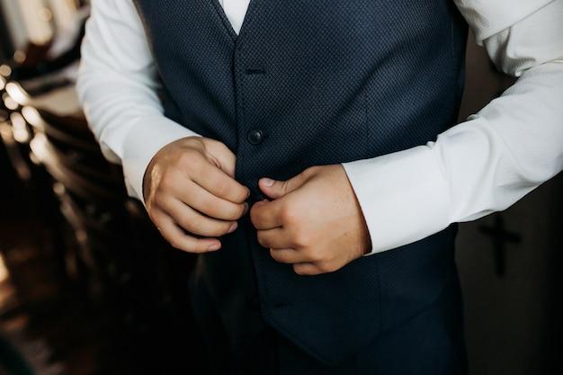 Un hombre con un traje azul se abrocha la chaqueta, de cerca. empresario cambiarse de ropa. corrección tonal. estilo de moda.
