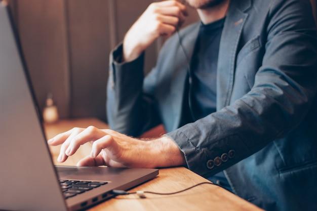 El hombre en traje azul con auriculares trabajando en una computadora portátil en café