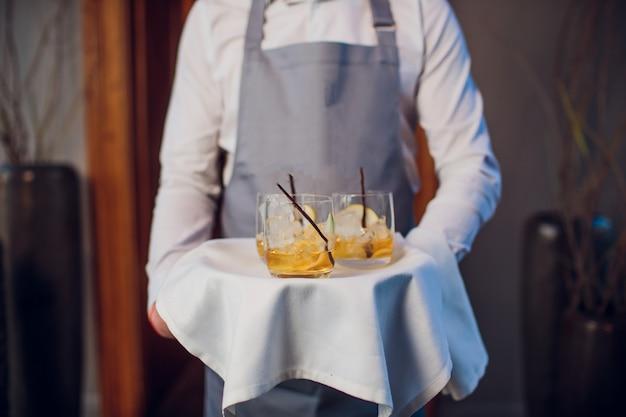 Hombre en traje con bandeja de plata con vasos de whisky