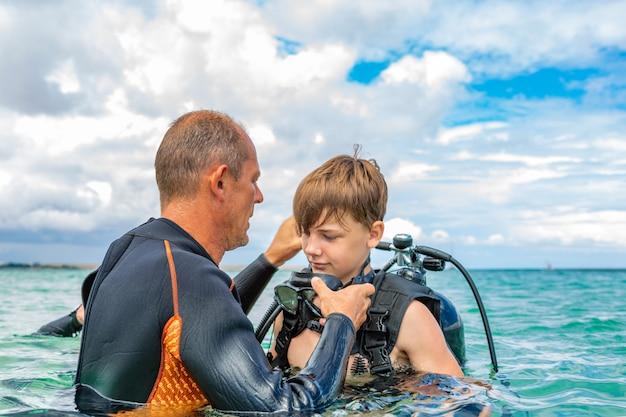 Un hombre en traje de buceo prepara a un niño para bucear