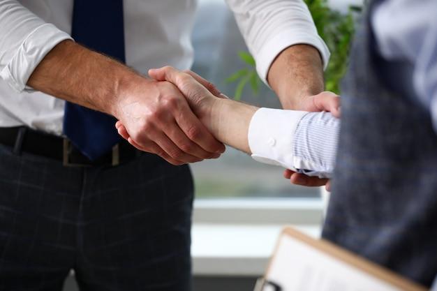 Hombre en traje y corbata dan la mano como hola en la oficina