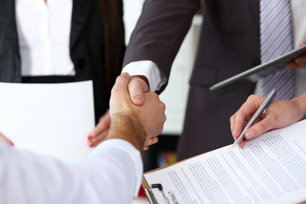 Hombre en traje y corbata dan la mano como hola en primer plano de la oficina