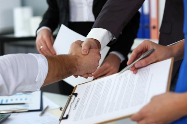 El hombre en traje y corbata dan la mano como hola en primer plano de la oficina.