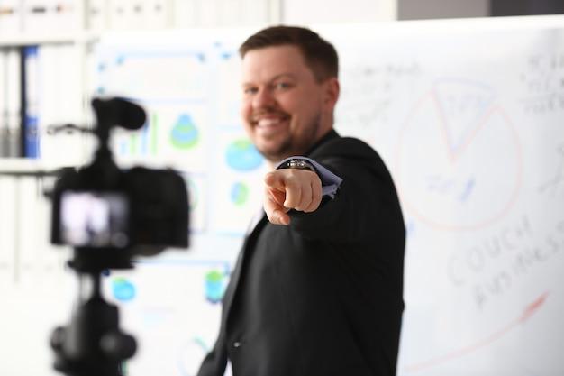 Hombre con traje y corbata muestra el panel gráfico de estadísticas haciendo videoblog promocional o una foto en la videocámara de la oficina al retrato del trípode. vlogger selfie solución o concepto profesional de información de gestión de asesor financiero