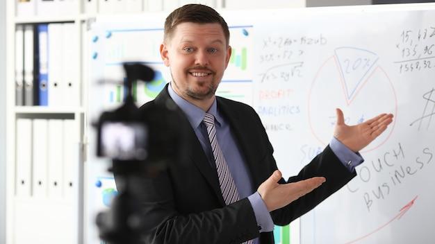 Hombre de traje y corbata muestra el panel de gráficos de estadísticas haciendo videoblog de promoción o sesión de fotos en la videocámara de la oficina al primer plano del trípode. solución de venta de selfies de vlogger o información de gestión de asesor financiero