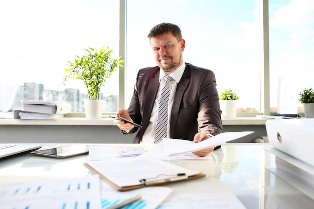 Hombre en traje y corbata sostenga en papeles de brazo en la oficina