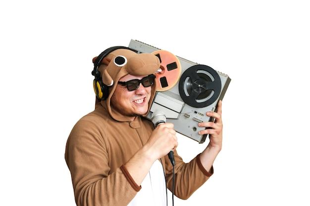 Hombre en traje de cosplay de una vaca cantando karaoke. chico en ropa de dormir de pijamas de animales con micrófono. foto divertida con grabadora de carrete. ideas de fiesta. música disco retro. aislado sobre fondo blanco.