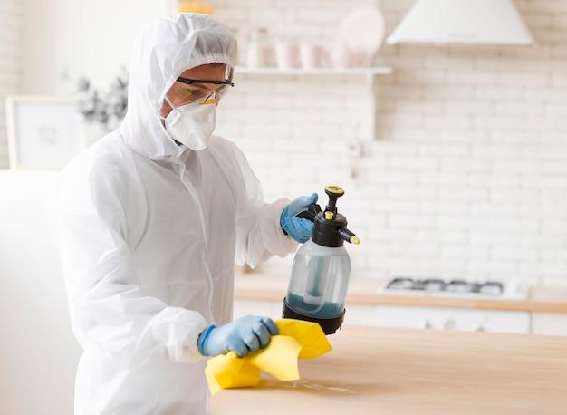Hombre en traje de desinfección de mesa