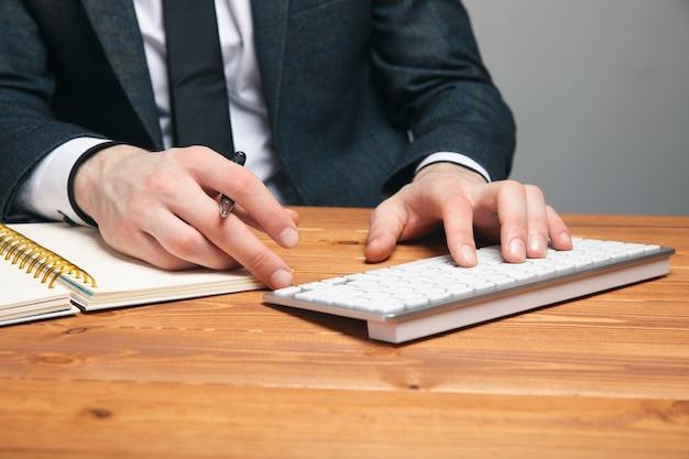 Un hombre con un traje escribe en un teclado sobre una superficie gris