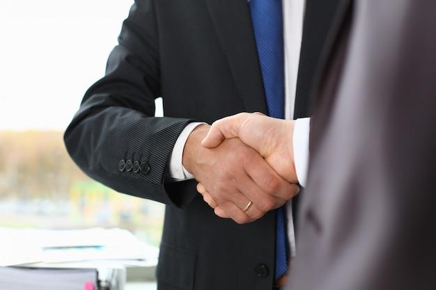 Hombre en traje estrechar la mano como hola en la oficina