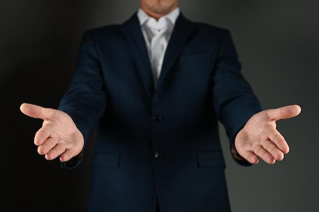 El hombre del traje extiende las palmas hacia adelante.