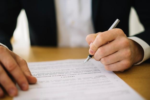 Hombre en traje de firmar contrato