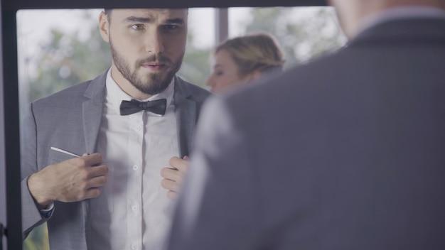 Hombre en traje formal vestirse en el vestidor