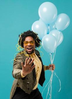 Hombre de traje y gafas de sol en la fiesta con retrato de globos