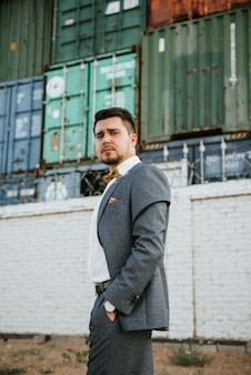 Un hombre con un traje gris posa en la calle para anunciar la ropa de los hombres. tiro para tienda de ropa masculina