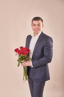 Hombre de traje gris con rosas rojas
