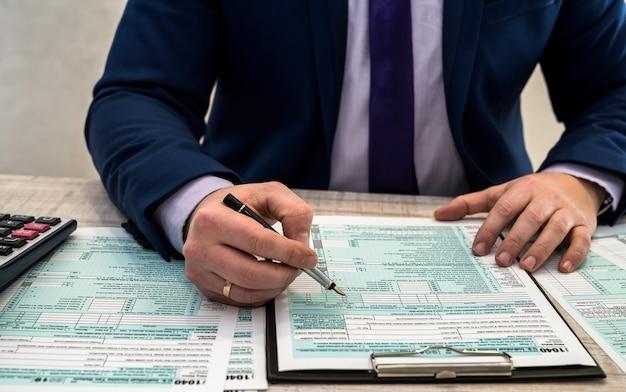 Un hombre de traje llena el formulario de impuestos 1040 individual de ee. uu. tiempo de impuestos. concepto de contabilidad