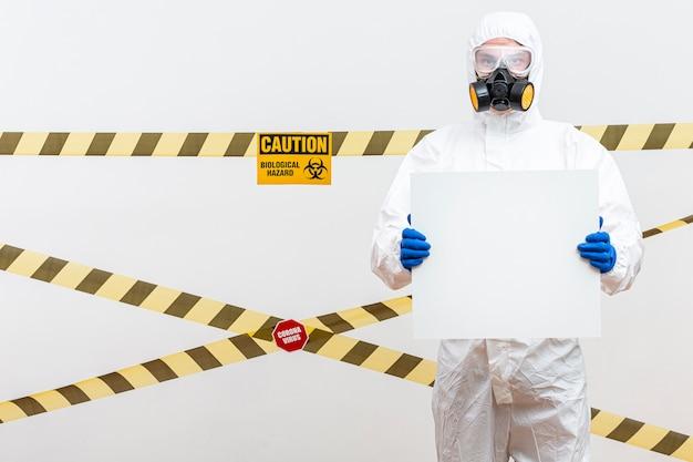 Hombre en traje de materiales peligrosos con un cartel en blanco