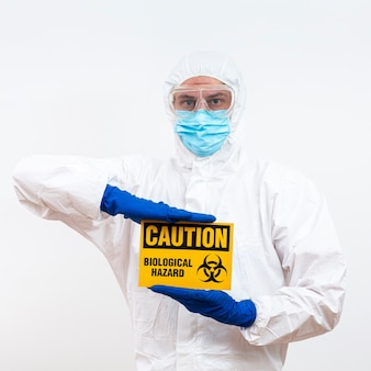 Hombre en traje de materiales peligrosos con señal de peligro