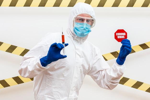 Hombre en traje de materiales peligrosos con señal de stop coronavirus
