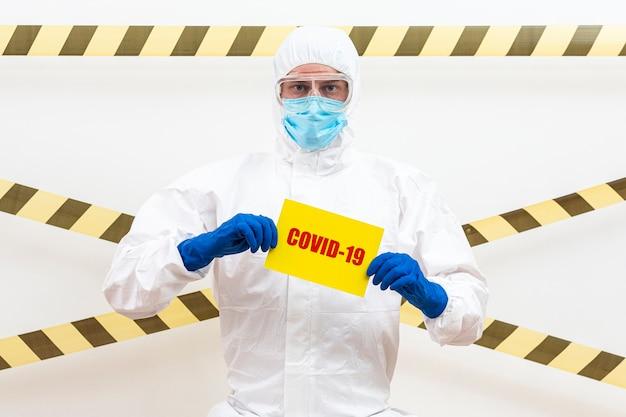 Hombre en traje de materiales peligrosos con signo covid-19