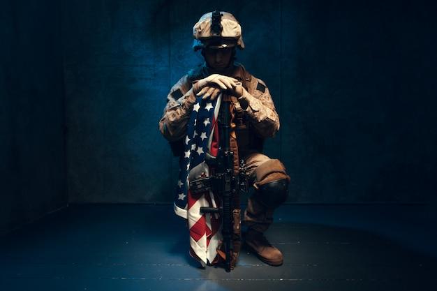 Hombre traje militar un soldado mercenario en los tiempos modernos con bandera estadounidense en estudio