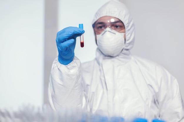 Hombre en traje de mono en laboratorio de microbiología con tubo de ensayo con sangre infectada con coronavirus. médico que trabaja con diversas bacterias y tejidos, investigación farmacéutica de antibióticos contra