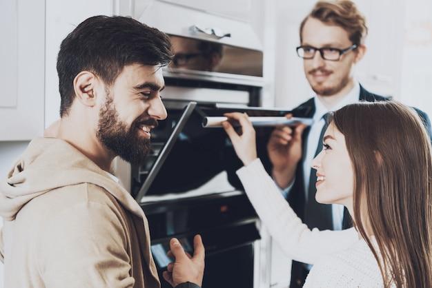 El hombre en traje está mostrando la estufa incorporada a la pareja