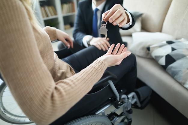 Hombre en traje de negocios dando las llaves del apartamento a la mujer discapacitada en primer plano de la silla de ruedas