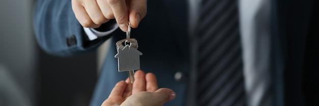 Hombre en traje de negocios entrega las llaves de la casa al primer plano de la mujer. asistencia social en concepto de construcción