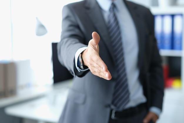 Hombre en traje de negocios estirando su mano para apretón de manos closeup