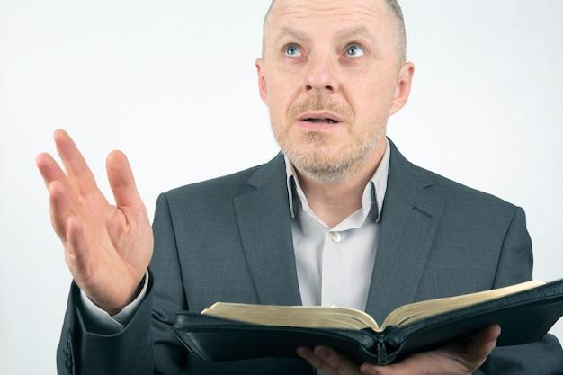 El hombre en un traje de negocios está leyendo la biblia.