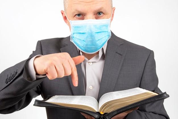 El hombre en un traje de negocios con una máscara médica en su rostro está estudiando la biblia.