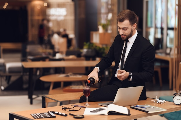 El hombre en traje de negocios está sosteniendo la botella de vino en su mano.