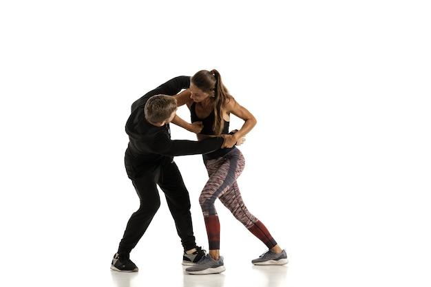 Hombre en traje negro y atlética mujer caucásica peleando sobre fondo blanco de estudio. autodefensa de las mujeres, derechos, concepto de igualdad. enfrentar la violencia doméstica o el robo en la calle.