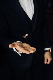 El hombre del traje negro está lanzando dos anillos de boda