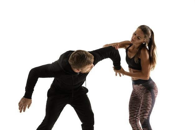 Hombre en traje negro y mujer atlética peleando en la pared blanca del estudio