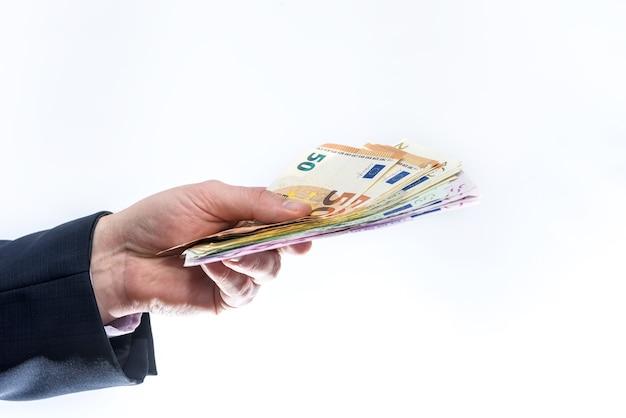 Hombre en traje ofreciendo billetes en euros aislado en blanco