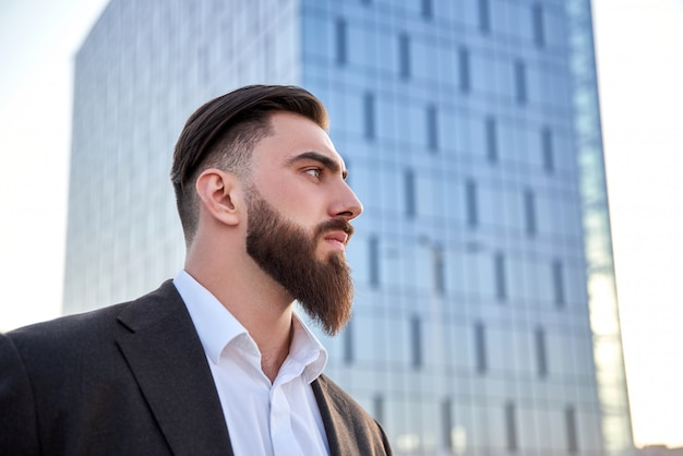 Hombre en traje de pie en frente de rascacielos llamando con él trabajar en la oficina. joven empresario caucásico.