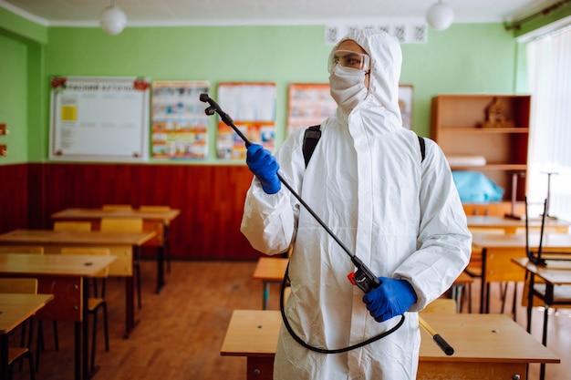 Un hombre con traje protector antibacteriano limpiando el aula con un spray con líquido desinfectante. el trabajador sanitario profesional desinfecta el auditorio con equipo especial. concepto de salud.