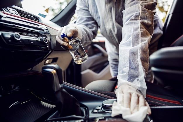 Hombre con traje protector con máscara desinfectando el interior del coche, limpiando las superficies que se tocan con frecuencia, previene la infección por coronavirus, la contaminación de gérmenes o bacterias. infección