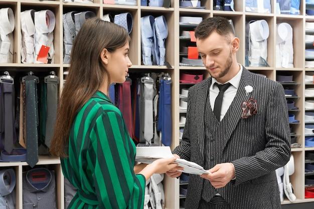 Hombre en traje de rayas elegir camisa, asistente proponiendo.