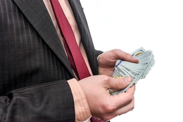 Hombre en traje sosteniendo pila de billetes de dólar