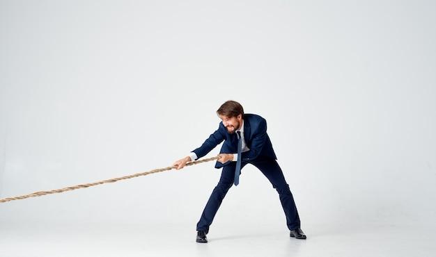 Un hombre en un traje tira de la cuerda fondo claro de la oficina de carrera