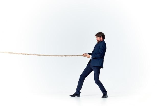 Un hombre en un traje tira de la oficina de trabajo de emoción de cuerda